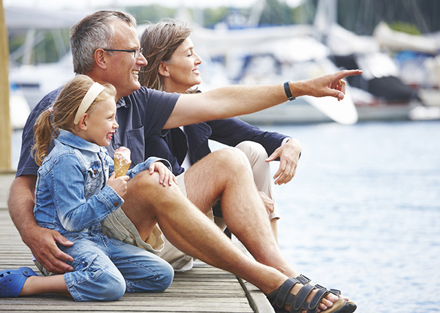 Happy Grandparents sitting with their granddaughter on a pier, pointing out at the boats.